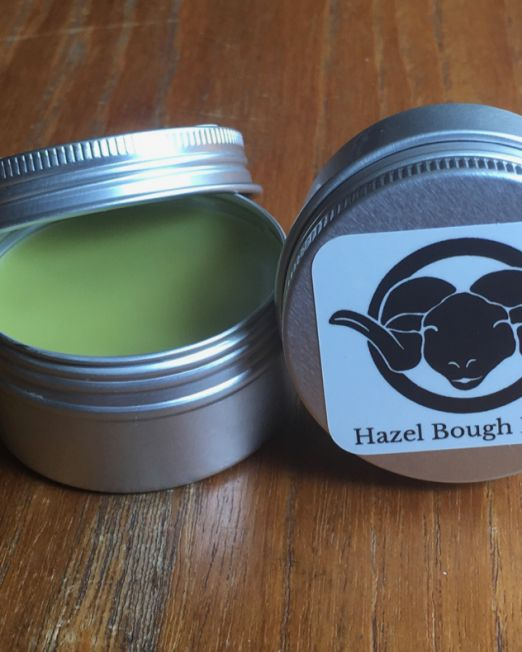 "an open tin of green herbal salve next to a closed one with a picture of a black sheep head logo and the text ""Hazel Bough Farm"", both on a brown wooden table"